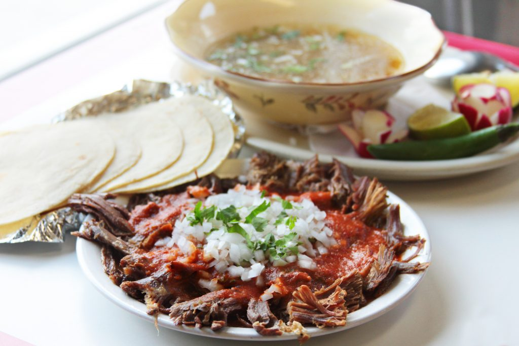 Mexican meat in a specialty Mexican dish with tortillas and sopa in the background