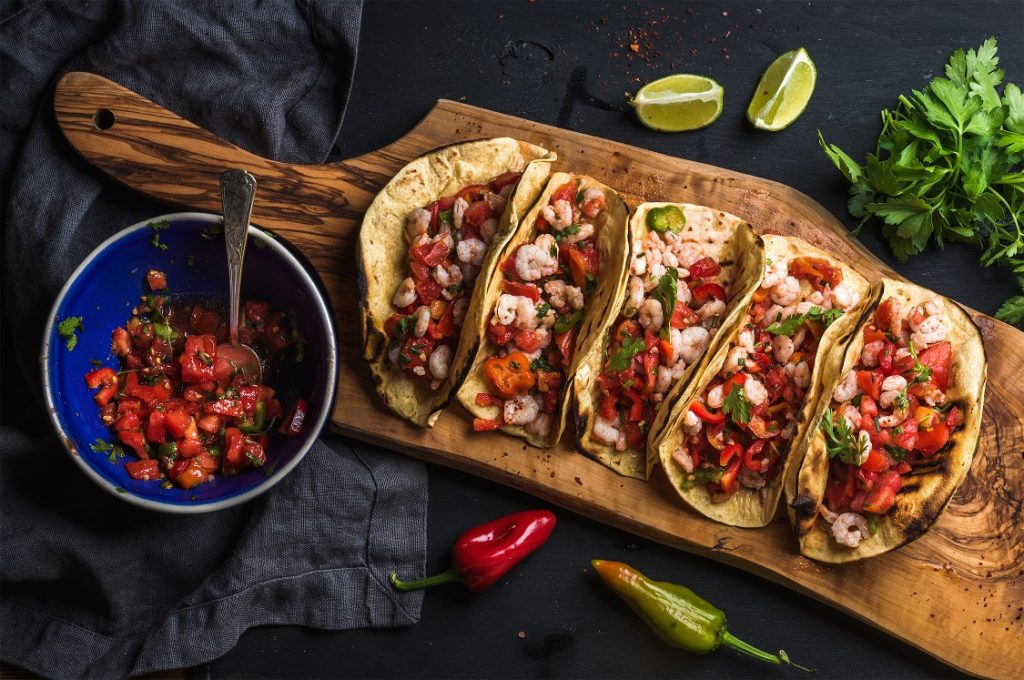 Mexican food- tacos on a wooden slab next to a dish of salsa surrounded by garnishes