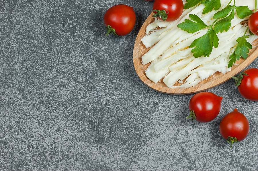 White asadero cheese with tomatoes and greens on cutting board.