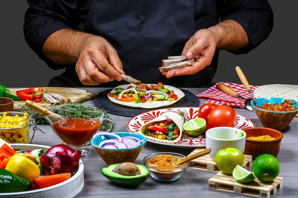 A street vendor preparing a Mexican dish